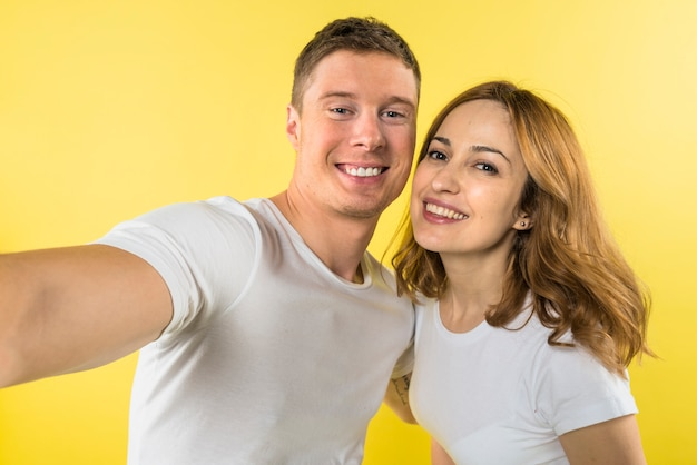 Portrait of a smiling young couple taking selfie against yellow backdrop Free Photo