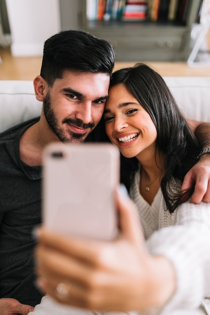 Portrait of smiling young couple taking selfie on mobile phone Free Photo