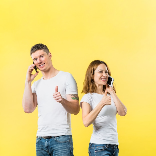Portrait of smiling young couple talking on mobile phone showing thumb up sign against yellow backdrop Free Photo