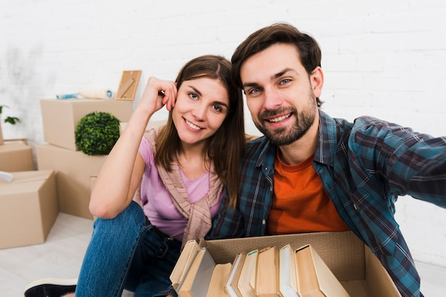 Portrait of a smiling young couple with books in the cardboard box taking sulfide Free Photo