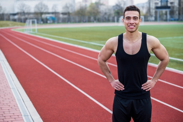 Portrait of a smiling young male athlete standing on race track Free Photo