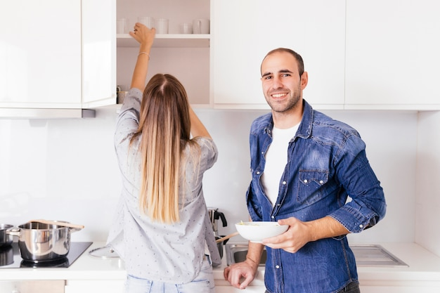 Portrait of a smiling young man holding bowl in hands standing near his wife in the kitchen Free Photo