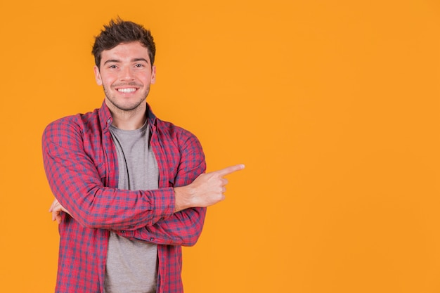 Portrait of a smiling young man pointing his finger against an orange backdrop Free Photo