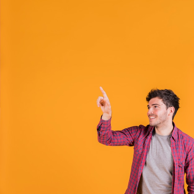 Portrait of a smiling young man pointing his finger against orange background Free Photo