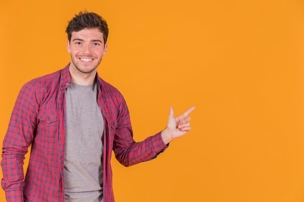 Portrait of a smiling young man pointing his finger on an orange background Free Photo