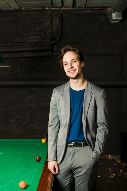 Portrait of a smiling young man posing near billiard pool in club Free Photo