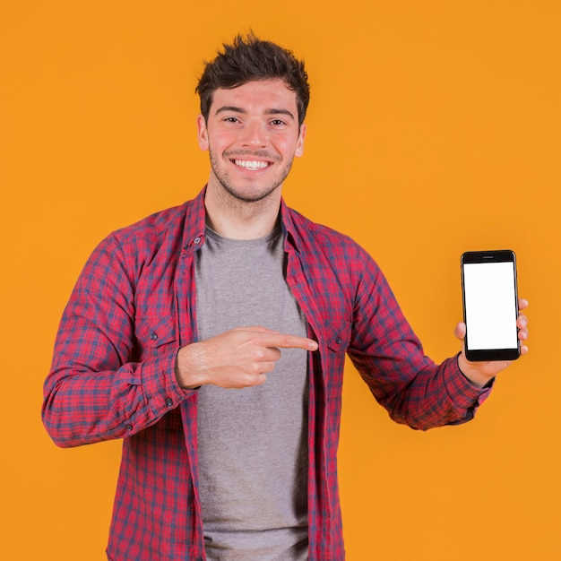 Portrait of a smiling young man showing his mobile phone against an orange backdrop Free Photo