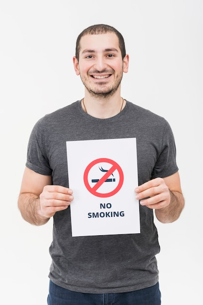 Portrait of a smiling young man showing no smoking sign isolated on white backdrop Free Photo