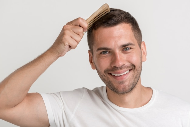 Portrait Of Smiling Young Man In White T Shirt Comb His Hair