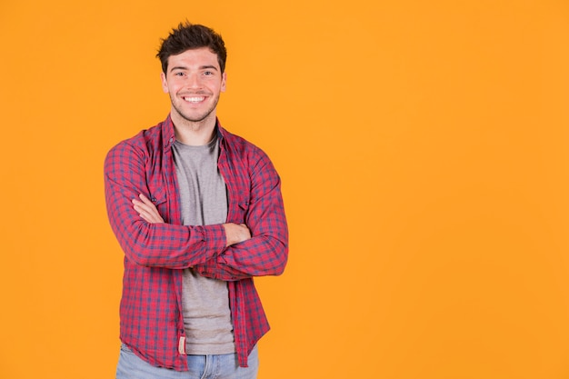 Portrait of a smiling young man with his arms crossed looking at camera Free Photo