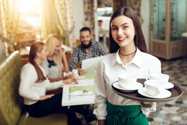 Portrait smiling young waitress standing in cafe Premium Photo