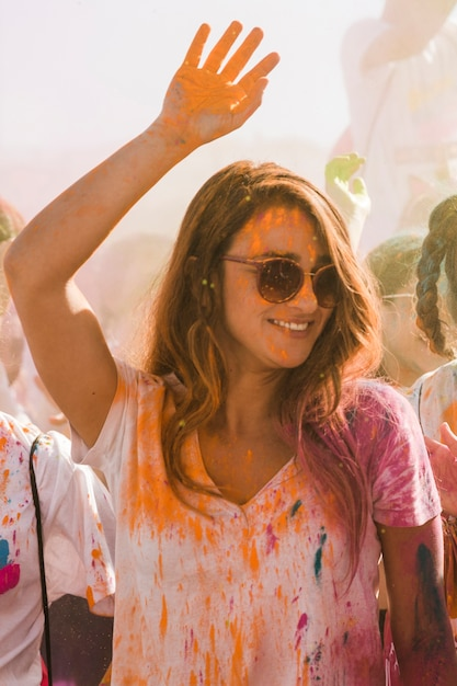 Portrait of a smiling young woman celebrating holi festival Free Photo