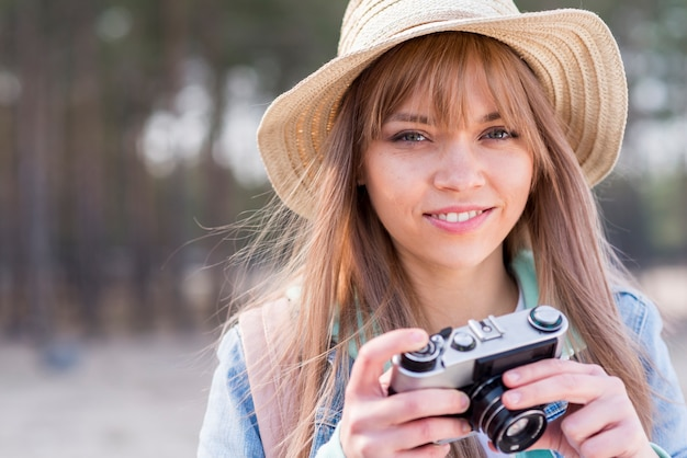 Portrait of a smiling young woman holding camera in hand looking at camera Free Photo