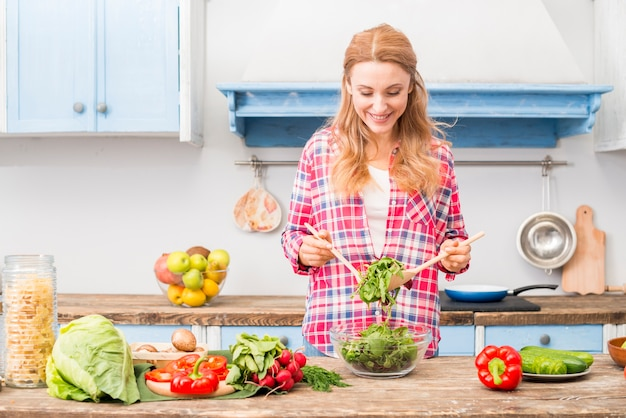 Portrait of a smiling young woman holding fresh spinach with wooden spoon Free Photo
