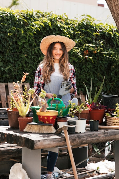 Portrait of a smiling young woman holding gardening gloves standing behind the plants on table Free Photo