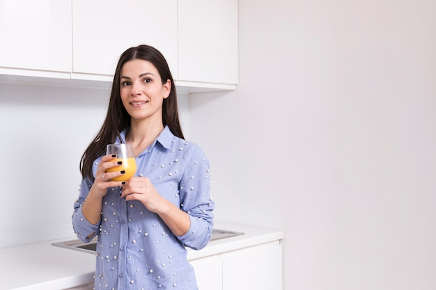 Portrait of a smiling young woman holding juice glass in hand looking at camera Free Photo