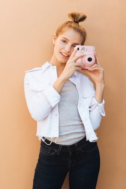 Portrait of a smiling young woman holding pink instant camera against beige backdrop Free Photo