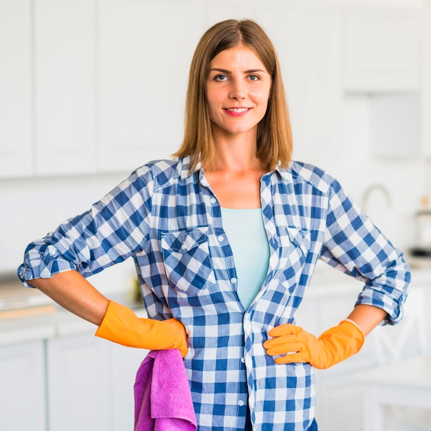 Portrait of smiling young woman holding pink napkin with her hands on hip Free Photo