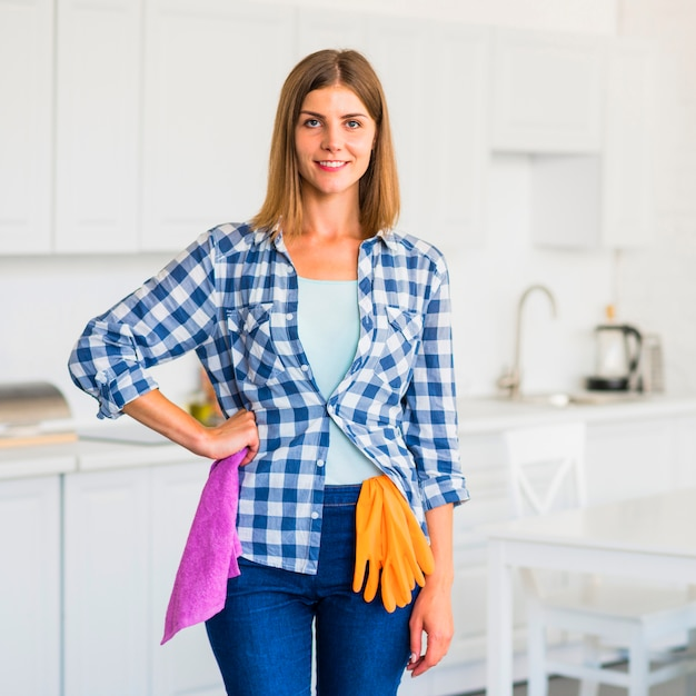 Portrait of smiling young woman holding pink napkin with an oranges gloves hanging over jeans Free Photo