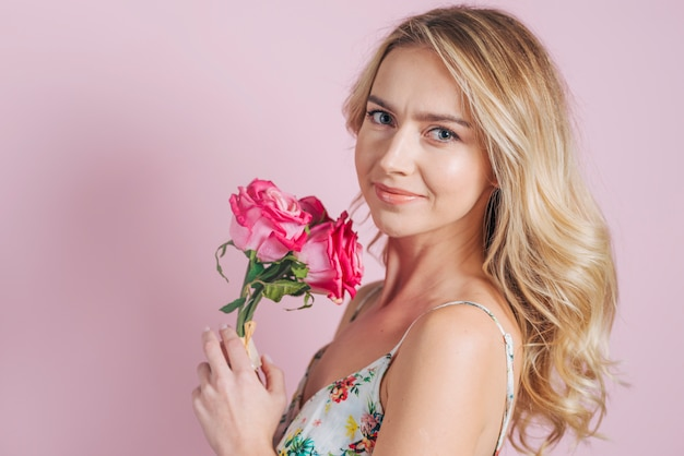 Portrait of smiling young woman holding pink roses against pink backdrop Free Photo