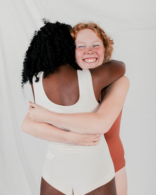 Portrait of a smiling young woman hugging her african friend against grey backdrop Free Photo