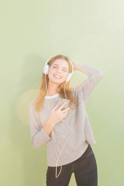 Ritratto di una giovane donna sorridente che ascolta la musica sulla cuffia contro il fondo verde della menta Foto Gratuite