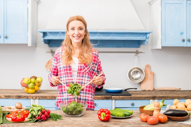 Portrait of a smiling young woman preparing the vegetable salad in the kitchen Free Photo