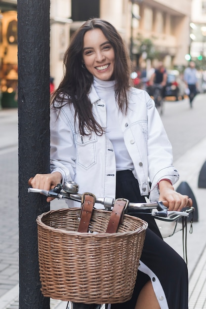 Portrait of a smiling young woman sitting on bicycle at street Free Photo