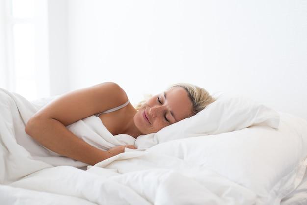 Ritratto di giovane donna sorridente dormire a letto Foto Gratuite