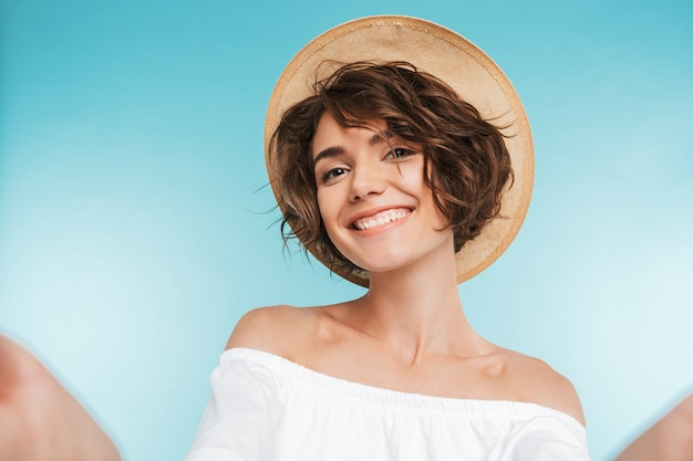 Portrait of a smiling young woman taking a selfie Premium Photo