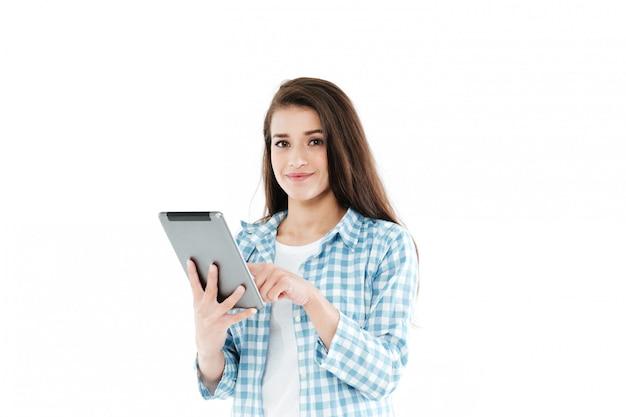 Ritratto di una giovane donna sorridente che per mezzo del computer della compressa Foto Gratuite