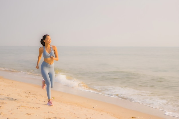 Portrait sport young asian woman prepare exercise or run on the beach sea ocean Free Photo