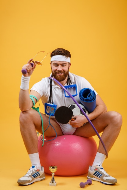 Portrait of a sports man sitting on a fitness ball Free Photo