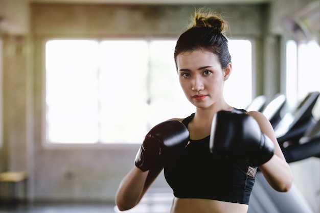 Portrait sporty girl beautiful woman with the back boxing gloves training at the gym Premium Photo
