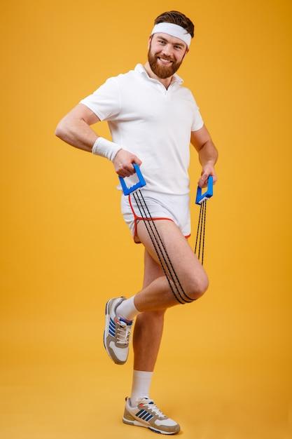 Ritratto di un uomo sportivo che si esercita con l'espansore di gomma Foto Gratuite