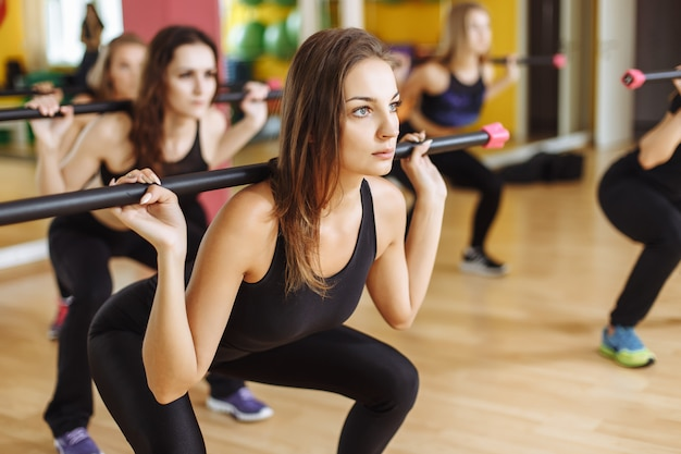 Portrait of sporty women exercising with barbell in fitness club Premium Photo