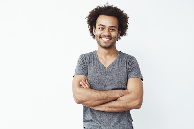 Portrait of stong and handsome african male student smiling with crossed arms over white wall. soon to be startup owner or salesman. Free Photo