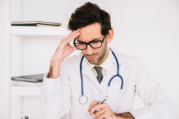 Portrait of a stressed male doctor Free Photo