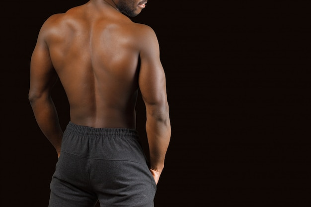 Portrait of a strong afro-american man showing off his physique on black Premium Photo