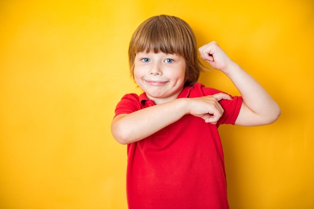 Portrait of a strong boy showing the muscles of his arms on yellow background Premium Photo