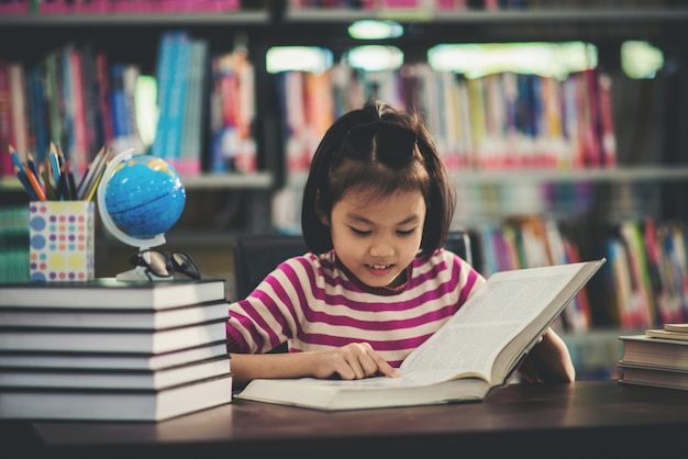 Portrait of a student child girl studying at library Free Photo