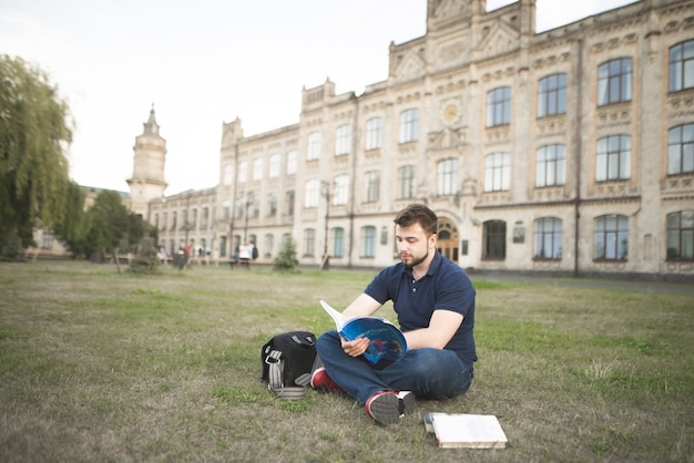 Premium Photo | Portrait of a student sitting on the grass and reading a book on the background of a beautiful old university.