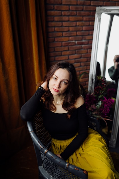 Portrait of a stunning fashionable woman sitting in a chair Free Photo
