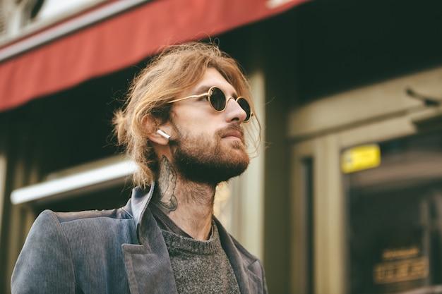 Portrait of a stylish bearded man in earphones Free Photo