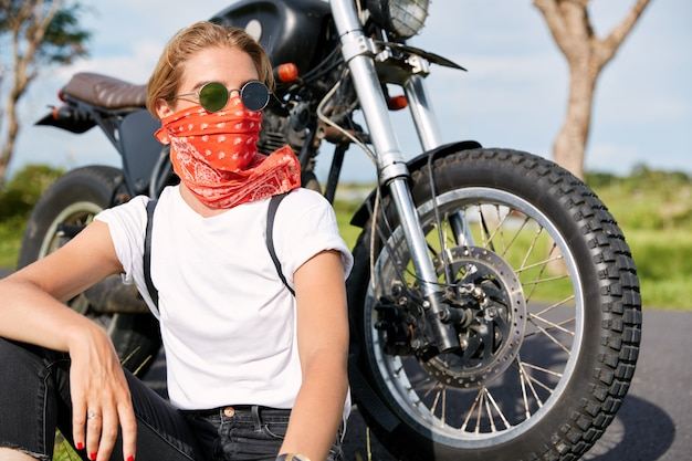Portrait of stylish female biker wears bandana and sunglasses, sits near fast motorbike, looks pensively away, has rest in open air after long ride, enjoys freedom and high speed. hobby concept Free Photo