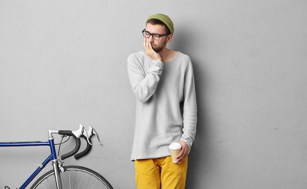 Portrait of stylish man keeping takeaway hot coffee, looking sad while having toothache, standing near bike, going to ride to university. young male hipster in fashionable clothes feeling pain Free Photo