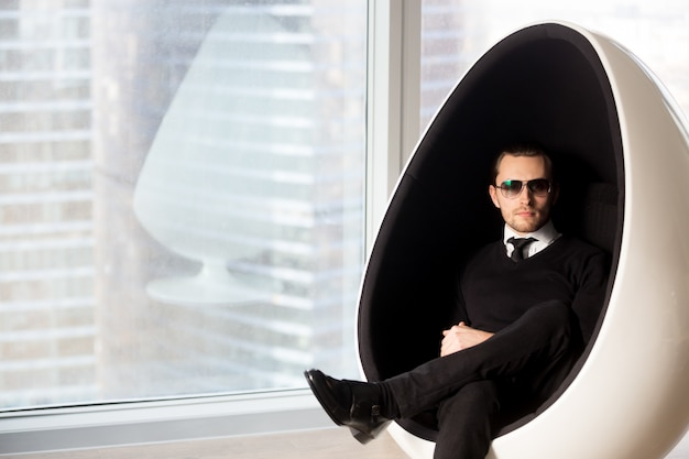 Portrait of stylish mysterious man in futuristic egg chair. Free Photo