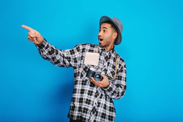 Портрет стильного удивленного красивого парня с камерой, картой, в шляпе с удовольствием. путешествие, отдых, выходные, позитивные эмоции, путешествие. Бесплатные Фотографии