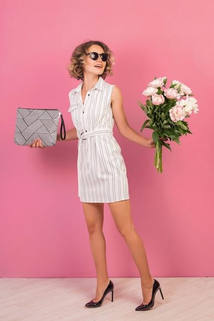 ハンドバッグと花の花束を保持しているエレガントな白い縞模様のドレスの肖像画のスタイリッシュな女性 無料写真
