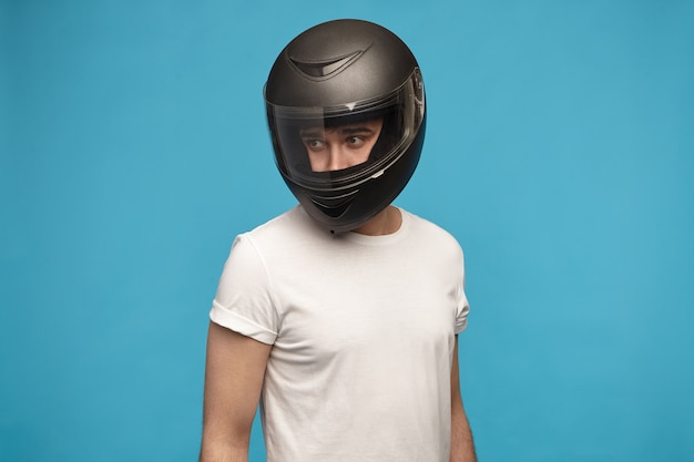 Portrait of stylish young man wearing white t-shirt and motorcycle helmet posing Free Photo